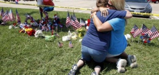 Maynard hugs her friend Atterton beside a growing memorial at the Armed Forces Career Center in Chattanooga